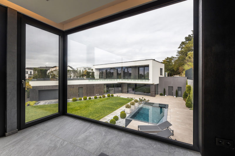 Pohľad z wellness domčeka na dom s hliníkovými oknami