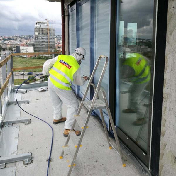 Pracovník SLovaktualu strieka tekutú fóliu na okná